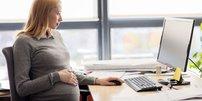 Schwangere Frau am Schreibtisch