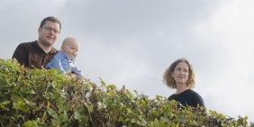 Vater, Sohn und Mutter an einer Gartenhecke.