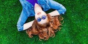 Junge Frau mit Sonnenbrille liegt auf einer Wiese