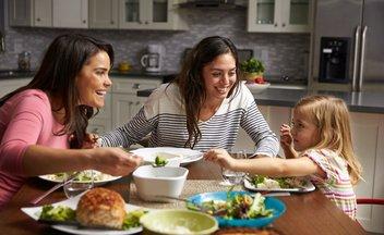Familie sitzt lachend beim Abendessen
