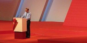 Redner vor Rednerpult auf einem großen Kongress